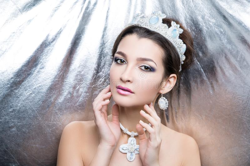 Woman white queen. Woman beauty queen close up portrait model. Massive jewellery made of beads, crystals earrings cross-stitch big cross. hair-do brunette hair royalty free stock image