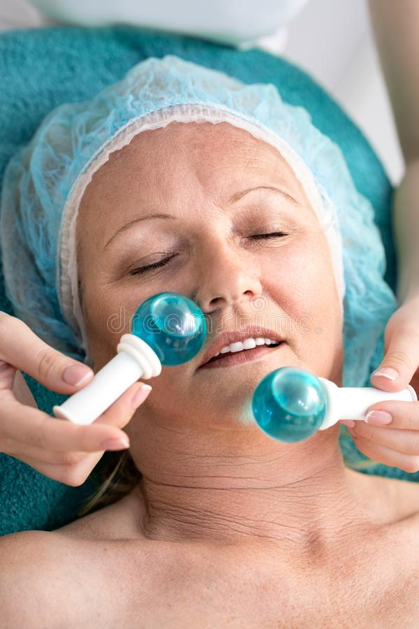 Woman in beauty salon during treatment with a cold glass balls stock photo