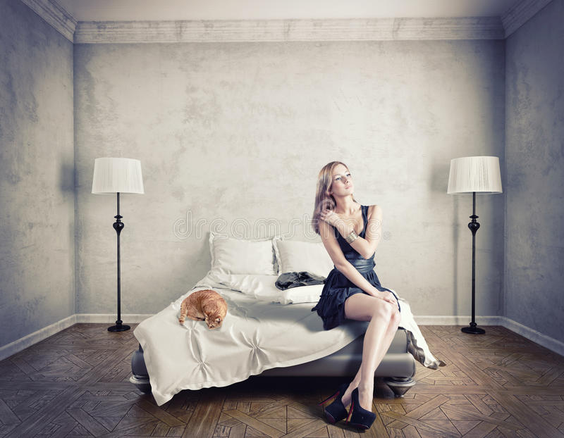 Woman on a bed. Young elegant woman sitting on a bed stock photography
