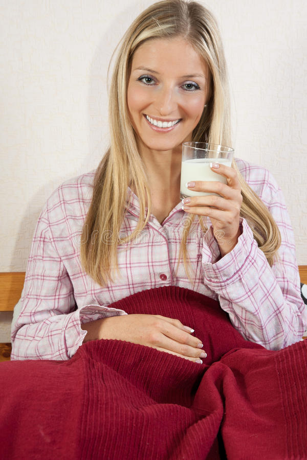 Woman in bed with glass of milk stock photography