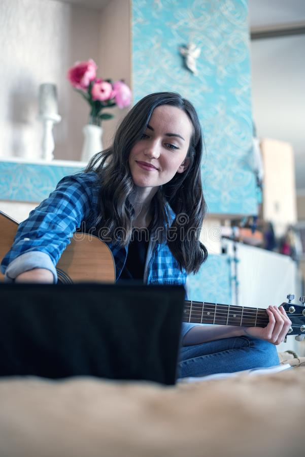 Woman on bed looking at laptop learning video for playing acoustic guitar.  stock photo