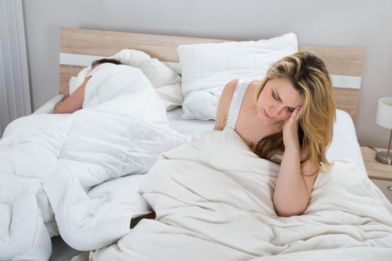 Woman on bed while man sleeping in bedroom stock image