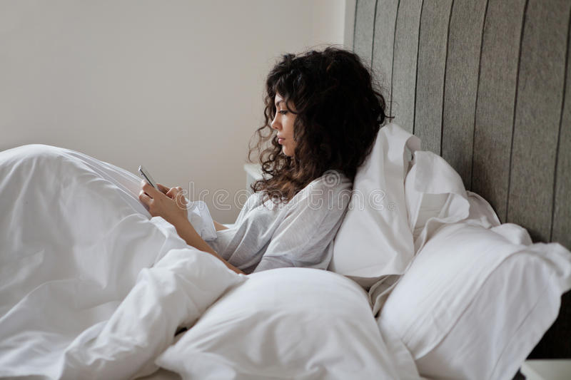 Woman in bed texting royalty free stock photo