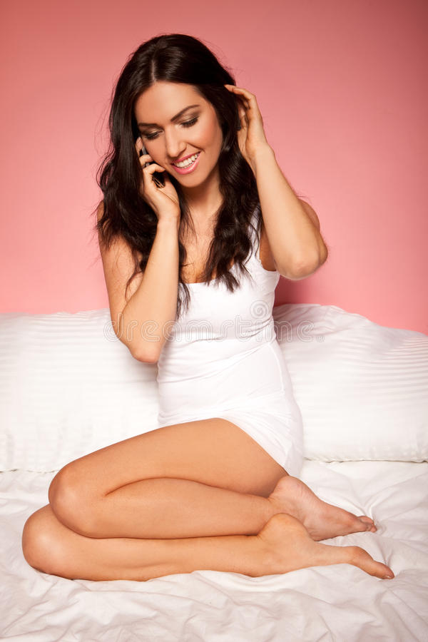 Woman On Bed Using Mobile. Beautiful brunette woman relaxing curled up on her bed talking on her mobile phone stock image