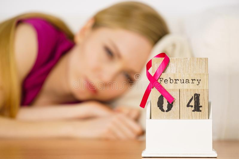 Woman on bed, world breast cancer day on calendar. Woman lying on bed looking at calendar, it is 4 february world breast cancer day, date with pink awareness royalty free stock photos