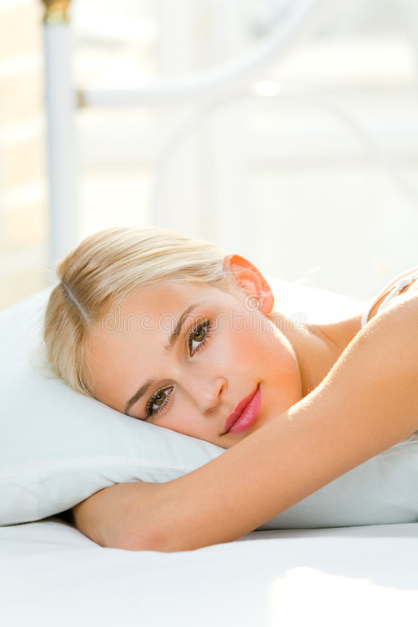 Woman at bedroom. Portrait of beautiful smiling woman on bed at bedroom royalty free stock photos