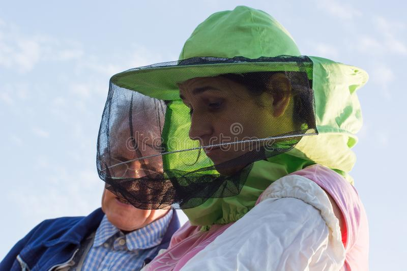 Woman beekeeper looks after bees in the hive royalty free stock image