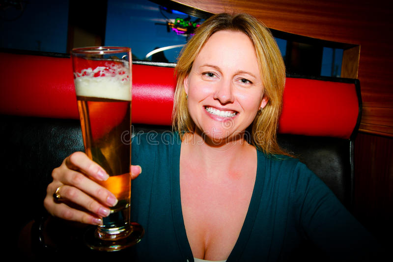Woman with Beer. A woman smiling holding a beer making a toast stock photography