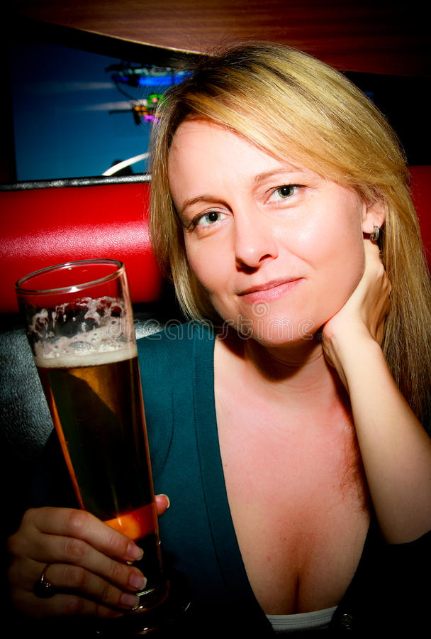 Woman with Beer. A woman smiling holding a beer stock images