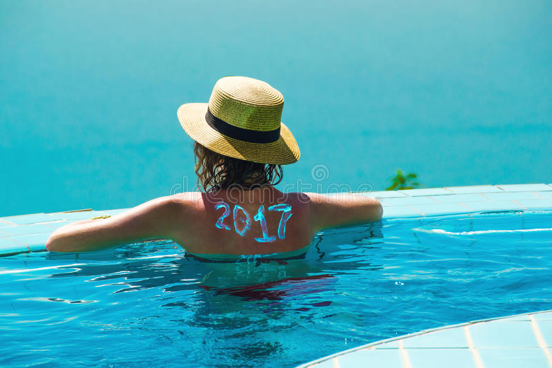Woman from behind in hat and infinity pool looking away. New travel season concept. 2017 written on back by suncream. Photo of the Woman from behind in hat and royalty free stock photography