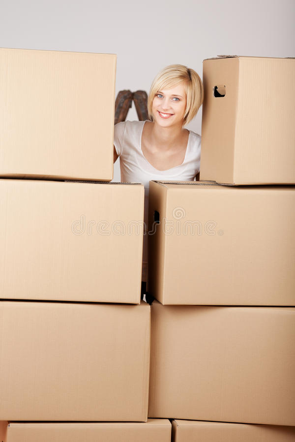 Woman Behind Stack Of Cardboard Boxes stock photos