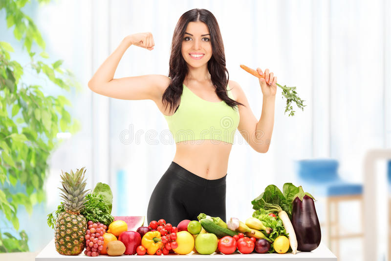 Woman behind a table with fruits and vegetables royalty free stock photos