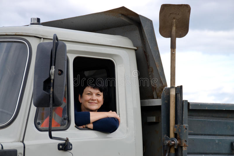 The woman behind the wheel of a truck. Portrait of middle-aged woman behind the wheel of a car stock image