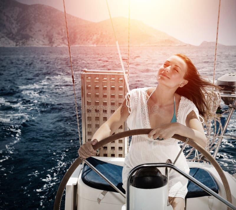 Woman behind the wheel yacht stock photos