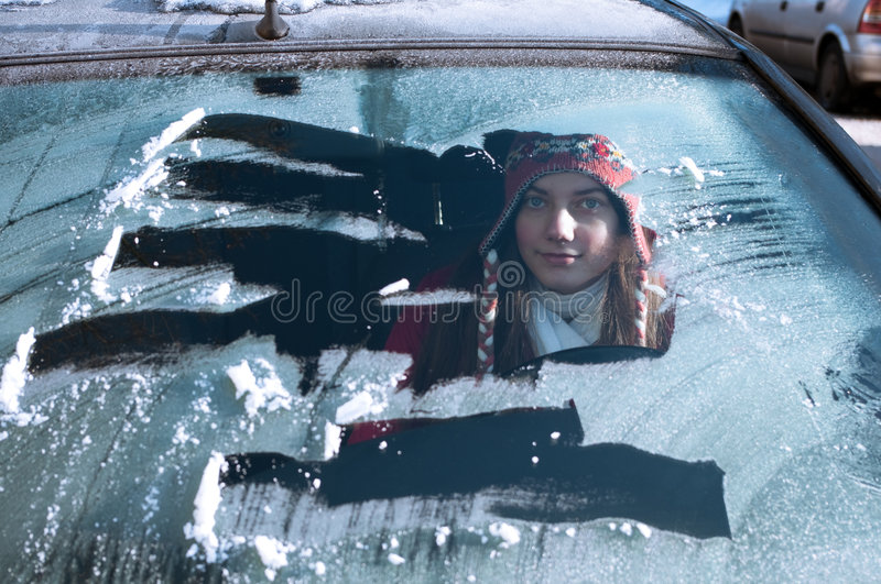 Woman behind windshield in winter. Woman looking through scraped windshield of a car royalty free stock photos