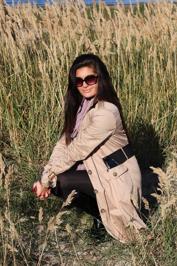 Woman in beige autumn coat sitting at beach