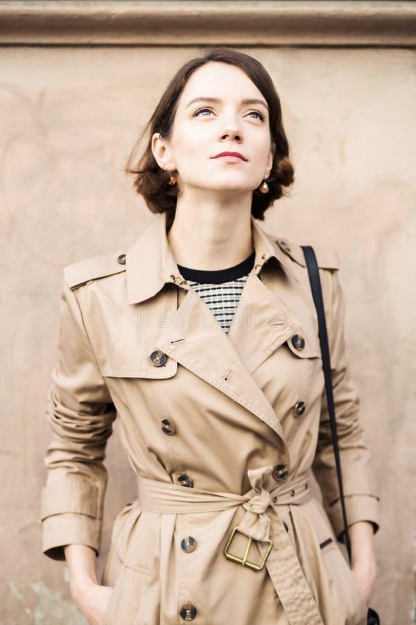Woman at beige coat with handbag looking up stock photos