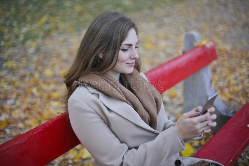 Woman in Beige Coat Holding Smartphone Sitting on Bench stock photos