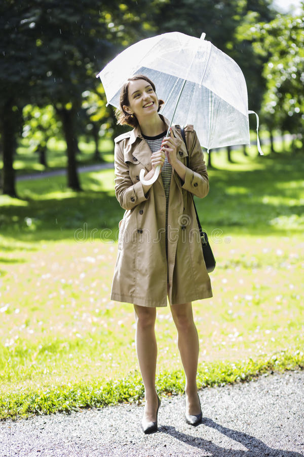 Woman at beige coat with umbrella under sunlight royalty free stock images