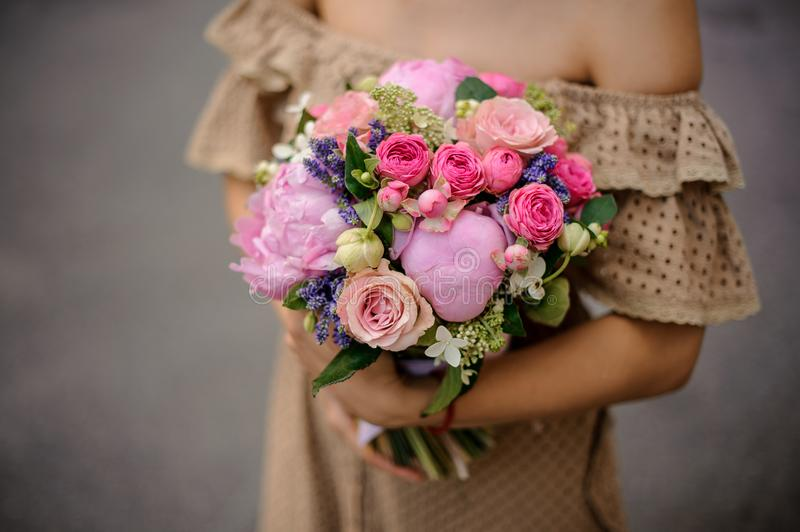 Woman in beige dress holding a lovely pink bouquet of flowers. Woman in beige dress holding a lovely pink bouquet of roses and peonies in her hands royalty free stock image
