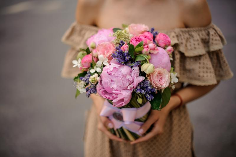 Woman in beige dress holding a romantic pink bouquet of flowers stock photos