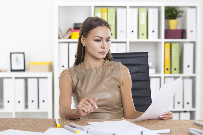 Woman in beige reading documents. Portrait of a woman in beige reading a document in her hand. She is at her workplace in a white office sitting at a cork table stock images