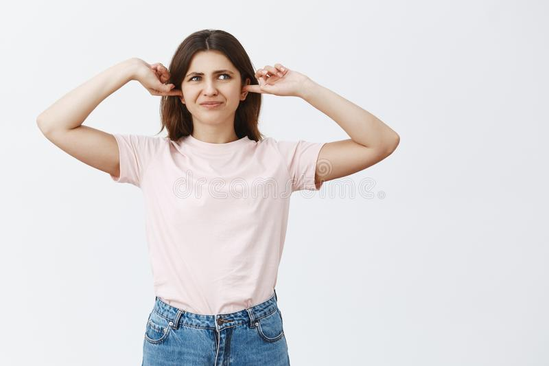 Woman being disturbed cannot concentrate hearing loud terrible noise covering ears with index fingers purisng lips and. Frowning from dislike and discomfort stock photography