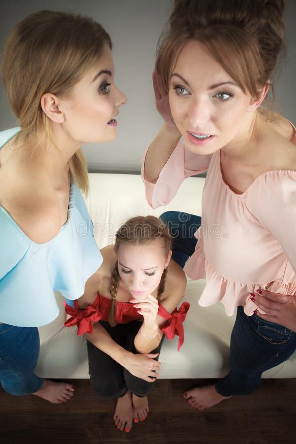 Woman being gossiped by two. Woman being gossiped bullied by two female friends. Friendship difficulties, rivaly and envy problems royalty free stock images