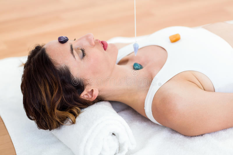 Woman being hypnotized with stones on her body royalty free stock image