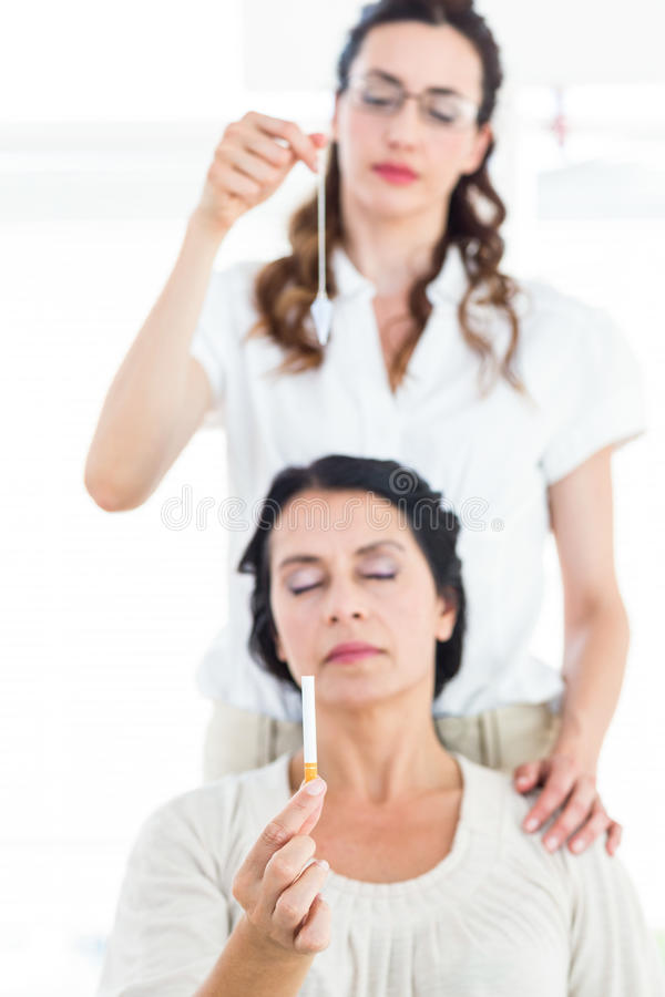 Woman being hypnotized to quit smoking. On white background stock photos