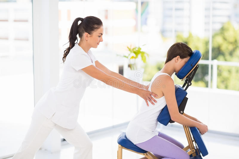 Woman being massaged on chair by masseuse royalty free stock image