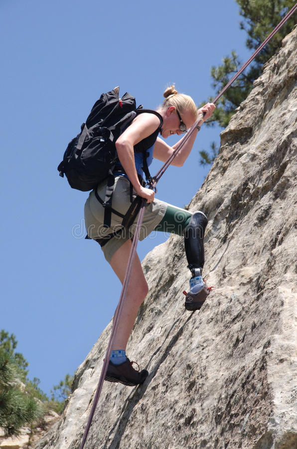 Woman belaying on rock face with prosthetic leg. royalty free stock images