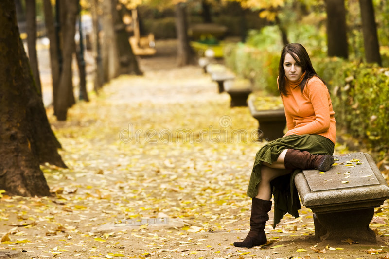 Woman in bench. Young pensive woman in bench royalty free stock photo