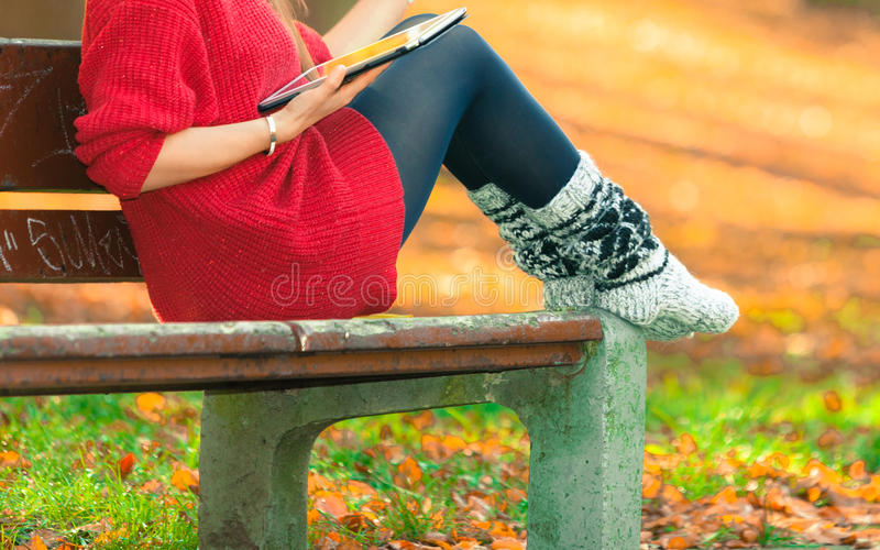 Woman on bench in park with tablet. Technology and education. Woman relaxing in autumnal park sitting on bench with tablet. Pretty fashionable female student stock photo