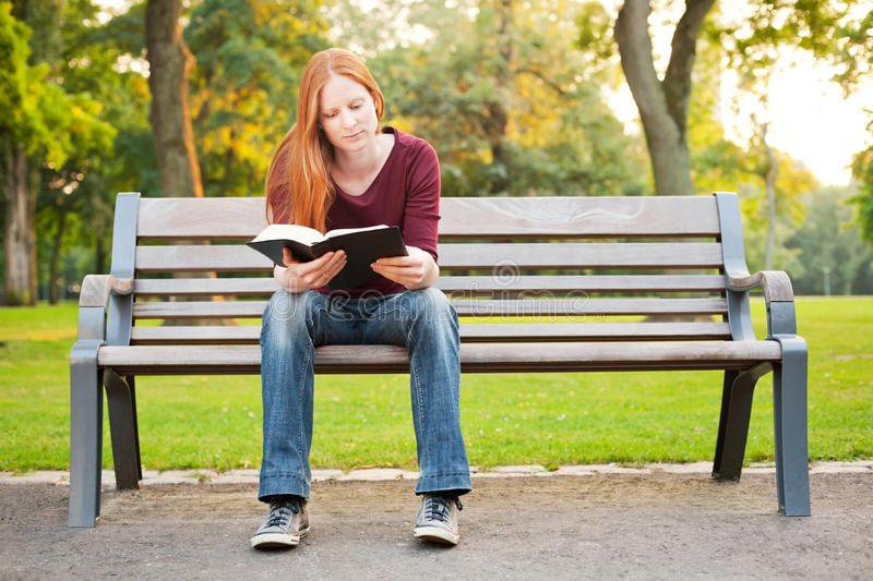 A Woman on a Bench Reading a Bible stock image