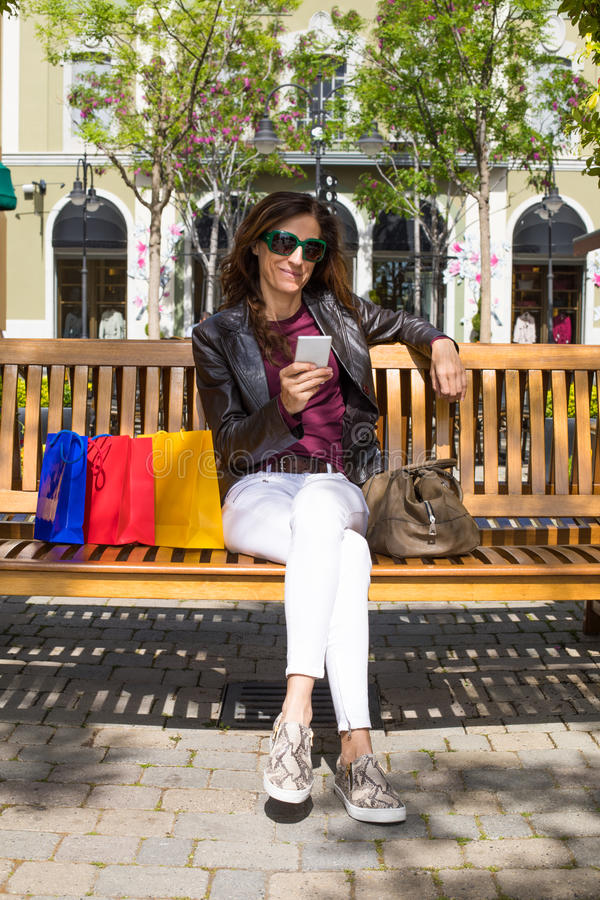 Woman in bench with shopping bags watching mobile vertical stock photography