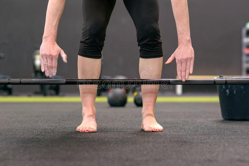 Woman bending over preparing to lift a barbell royalty free stock images
