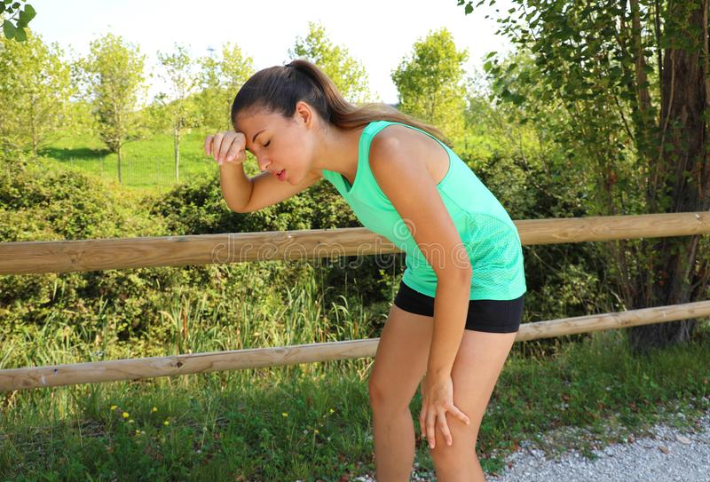 Woman bent over in exhaustion and catching her breath after a running session.  stock photos