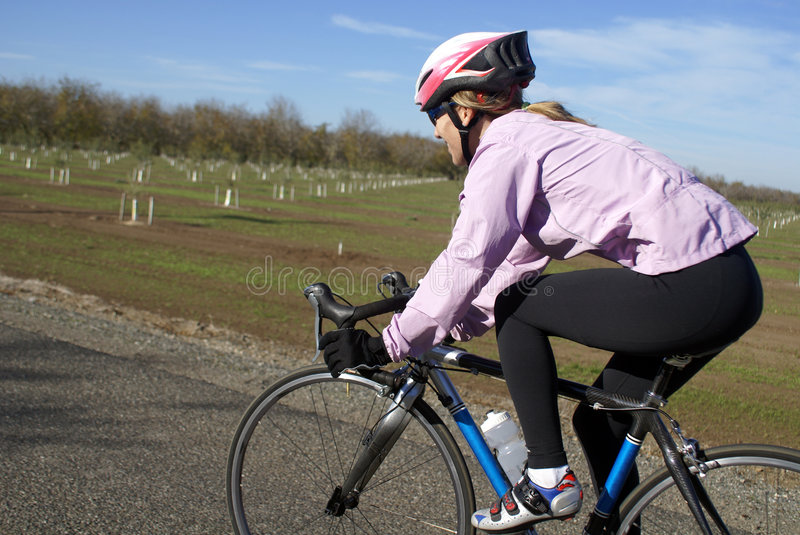 Woman on Bicycle. A woman on a bicycle rides along a country road royalty free stock photo