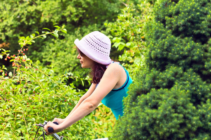 Woman on a bicycle. Woman in hat and sunglasses on a bicycle royalty free stock images