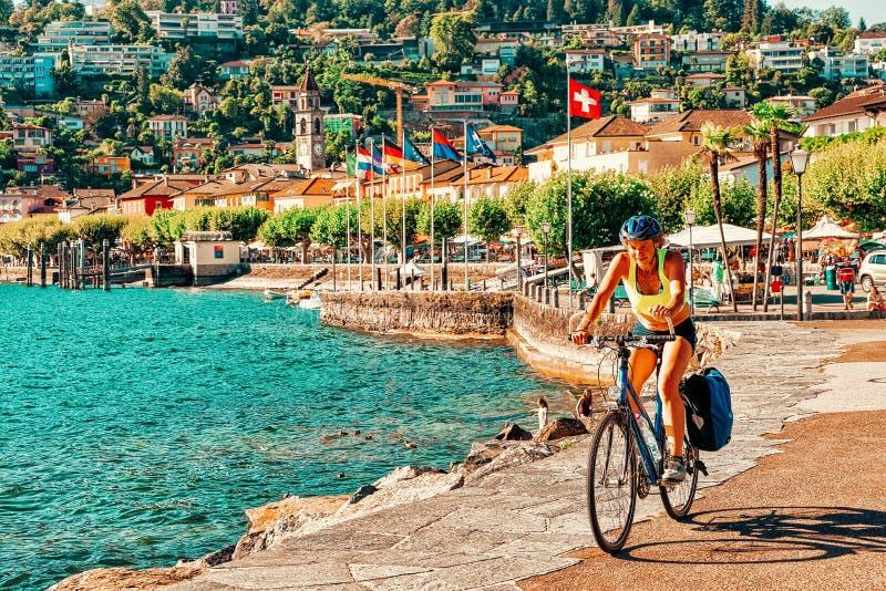 Woman on bicycle in Ascona luxury tourist resort promenade royalty free stock image