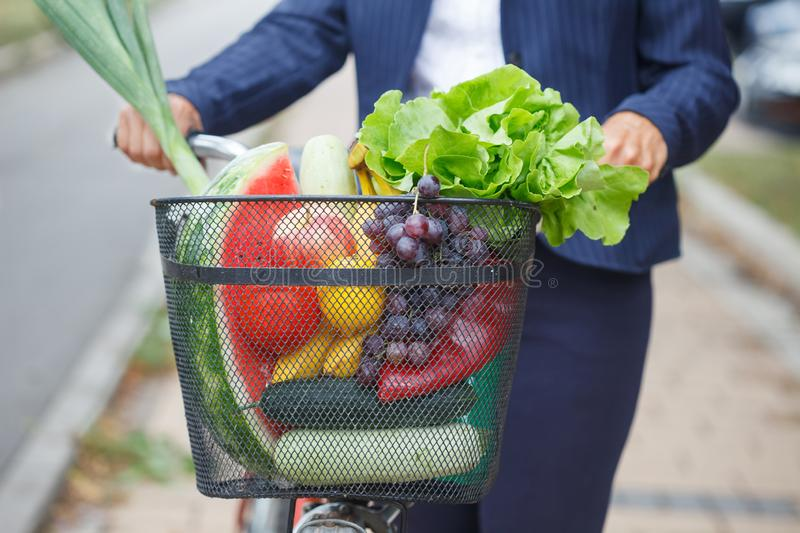 Woman with bicycle basket full of groceries stock photo