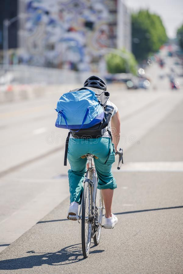 Woman cyclist with a large backpack rides a bicycle on the street of a modern city stock image
