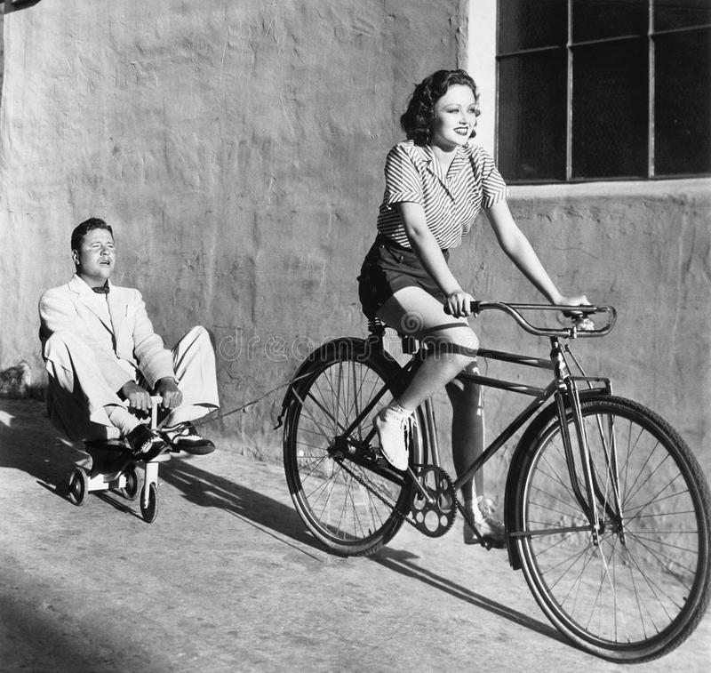 Woman on a bicycle pulling a grown man on a toy tricycle stock image