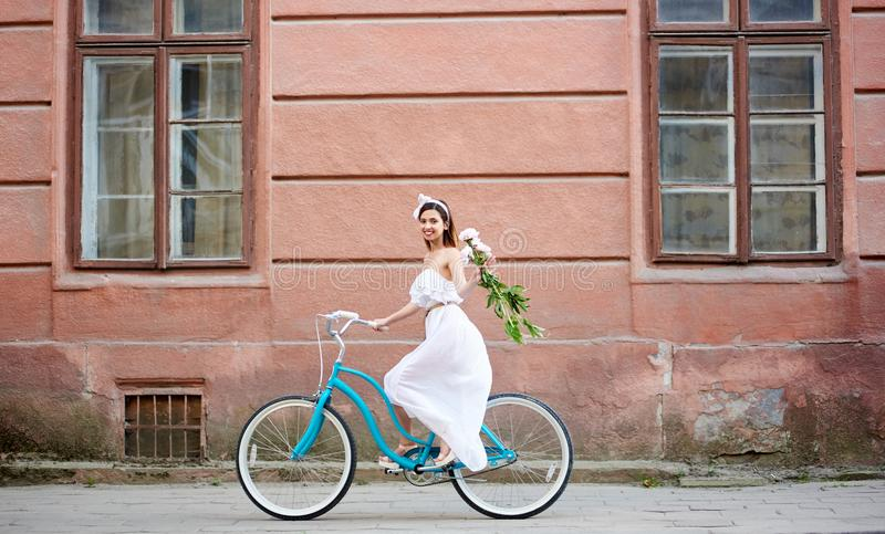 Woman on bicycle is riding along old city with peonies stock images