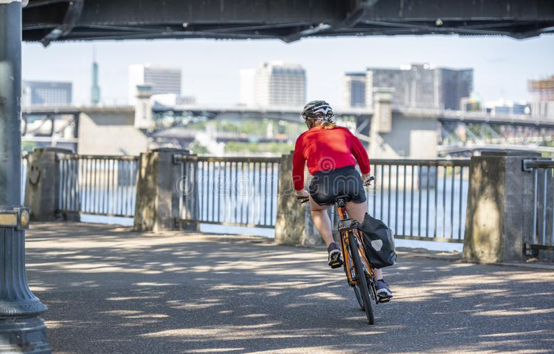 Woman on a bicycle turns onto the riverfront in Portland stock image