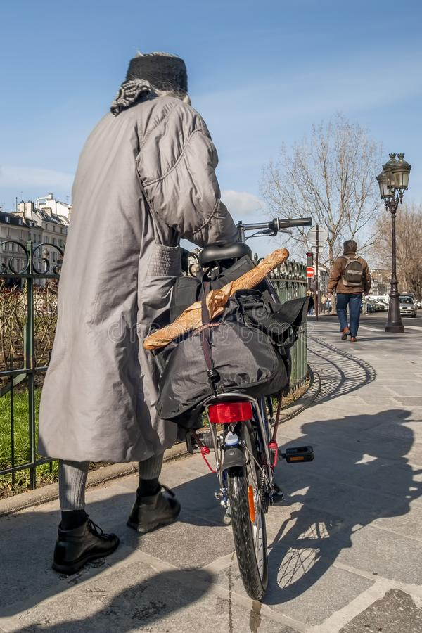 Woman with bicycle and typical French baguette on the streets of central Paris, France stock photos