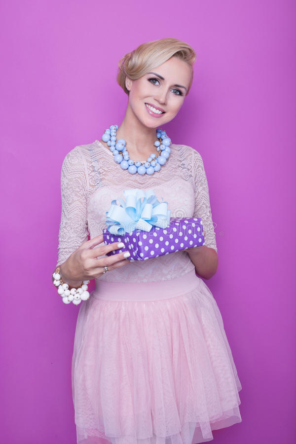 Woman with big beautiful smile holding purple present. Christmas. Holiday. Gift royalty free stock photo