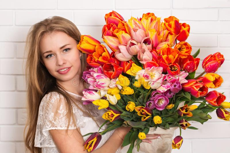 Woman with a big bouquet. Young beautiful woman with a big bouquet of tulips royalty free stock photos