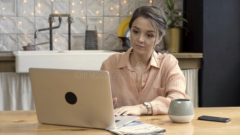 Woman with a big cup and her notebook in the kitchen of her modern apartment. Stock footage. Serious young female stock photos